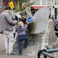 Kids playing on a giant ships propellor in the Scheepvaartbuurt at the Haarlemmerstraat