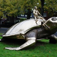 Jan Fabre riding an enormous gold sea turtle on his way to Utopia