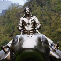Close-up of Jan Fabre riding an enormous gold sea turtle on his way to Utopia