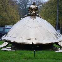 Jan Fabre Riding a giant gold sea turtle down the Apollolaan, crossing Beethovenstraat to Utopia