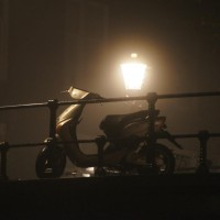 Scooter on a bridge, under a streetlamp, shrouded in mist.