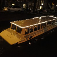 Electric saloon boat decorated for Christmas, cruising the 7 bridges.
