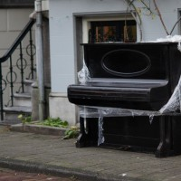 Abandoned street piano getting warped in the rain.