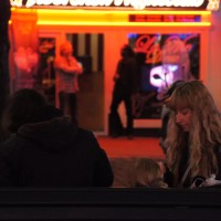 Mom feeding her tiny baby on a bench in front of a strip club.