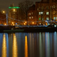 Ship (houseboat) on the Amstel decorated for the holidays. Okura Hotel behind it.
