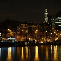 Amstel River, decorated houseboat, the old City Archives and Nederlandse Bank