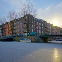 Frozen Amsterdam canal, early winter morning sun.