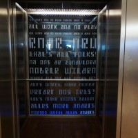 Stationary text on the wall behind the elevators seen through glass. Read fast as you ride!