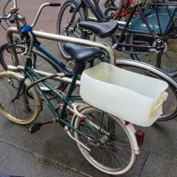 Creative cargo carrier. Empty oil container zip-tied to the bike rack.