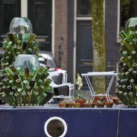 Closeup of Brouwersgracht houseboat with bottle trees and Agave plants