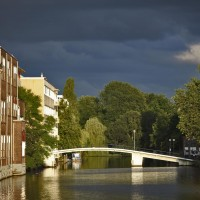 Pedestrian bridge to Amsterdam University in the evening light against a dark sky