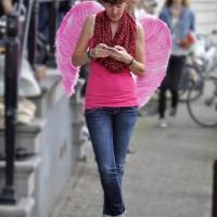 Beautiful angel texting along the parade route