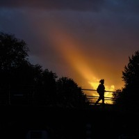 A single ray of light illuminates a girl walking along the Amstel River in Amsterdam