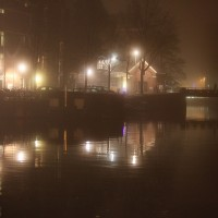 Foggy canal behind the Sluyswacht Café with solitary man walking.